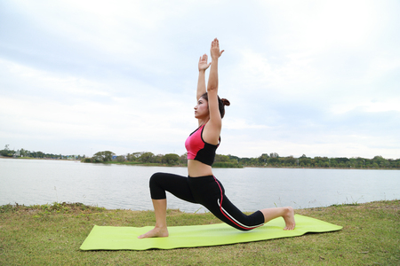 Young woman doing yoga exercise in the park photo