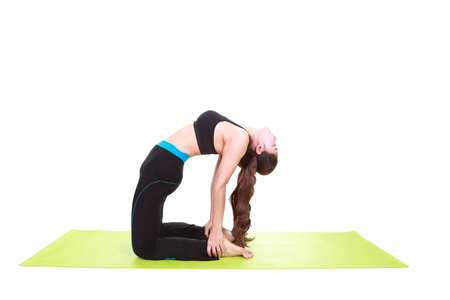 Young woman doing yoga exercise with yoga mat isolated on white background photo