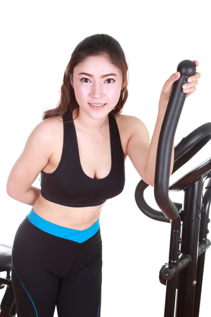 exercise machine: young woman doing exercises with exercise machine, on white background