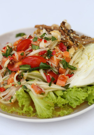 papaya spicy salad with salmon on white table in restaurant photo