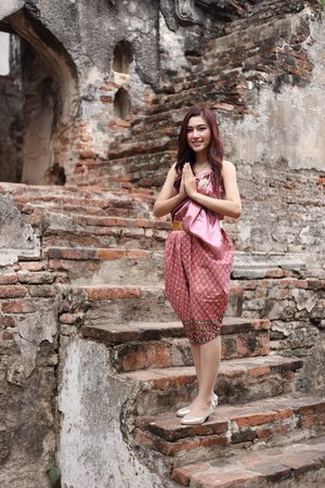 pay wall: Female pay respect in Thai traditional dress at  historical park