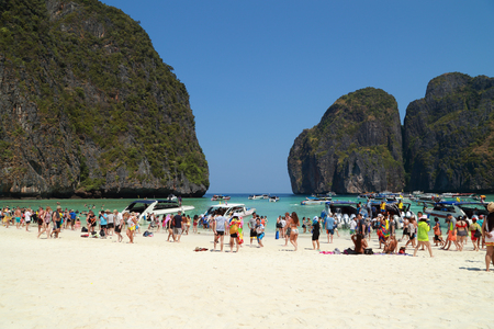 MAYA BAY, THAILAND - MARCH 15, 2015: Crowds of visitors enjoy a day trip at Maya Bay, one of the iconic beaches of Phi Phi islands, Krabi, Thailand