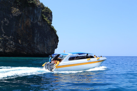 KOH PHI PHI, THAILAND - MARCH 16, 2015: speed boats with traveller on turquoise water of Koh Phi Phi island on March 16, 2015 in Koh Phi Phi island, Krabi, Thailand