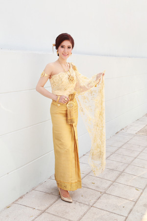 thailand art: woman with Thai dress and wall background Stock Photo
