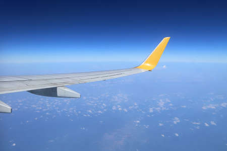 Wing of an airplane flying above the sky photo