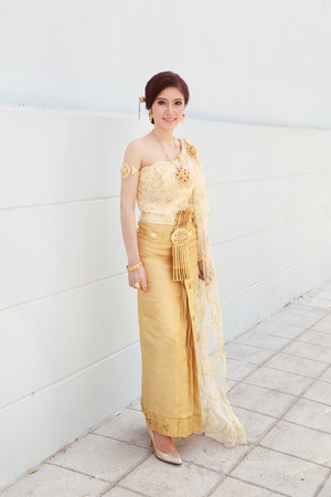 woman with Thai dress and wall background Banco de Imagens