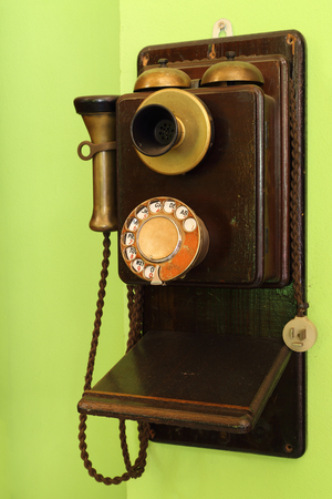 old classic wood telephone hanging on green wall Stock Photo