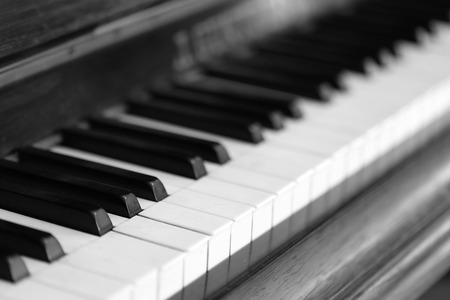 piano closeup: black and white piano keys and wood grain (soft focus)