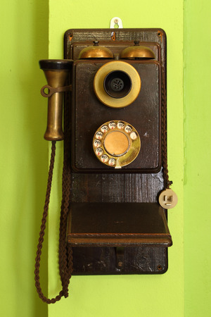 magneto: old classic wood telephone hanging on green wall Stock Photo