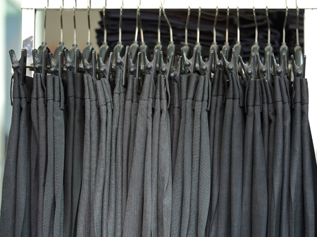 Mens dress pants trousers hanging in a retail shop Banco de Imagens