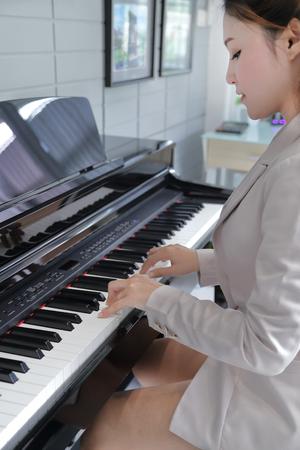 piano: Hermosa mujer joven que juega en el piano negro