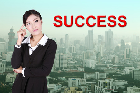 aha: business woman thinking about success with city background