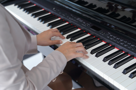 keyboard instrument: hands of a young woman playing piano