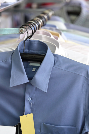shirts on hangers: Mens plaid shirts in different colors on hangers in a retail shop