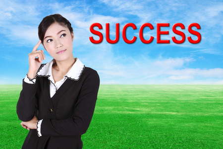 aha: business woman thinking about success with green grass field and blue sky background Stock Photo