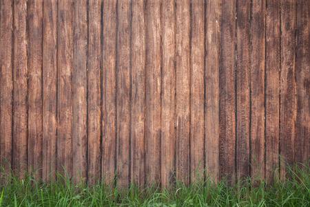 Fond de clôture en bois brun avec herbe verte Banque d'images - 46391304