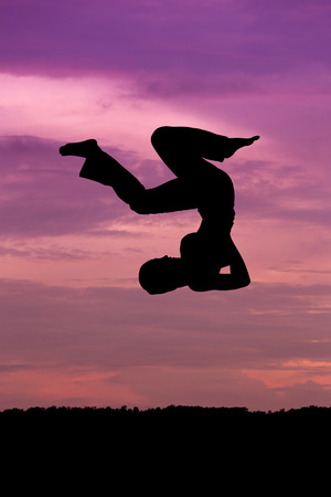 somersault: Silhouette of woman jumping at sunset