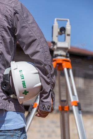 teodolito: Ingeniero con taqu�metro o teodolito para las columnas de l�nea de encuesta para la construcci�n de edificios Foto de archivo