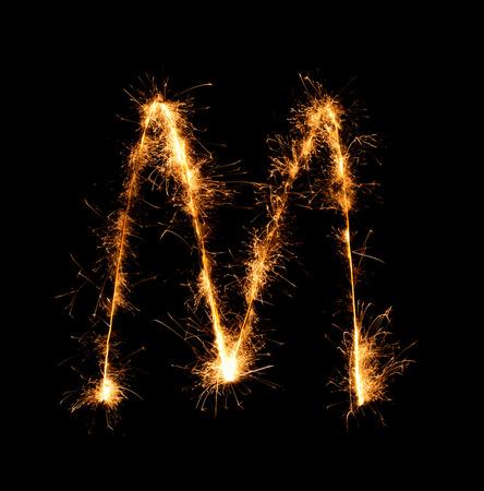 lettre alphabet: Sparkler feu d'artifice de lumi�re alphabet M (lettres majuscules) au fond de nuit Banque d'images