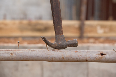 leverage: hammer pulling a nail out of wood at construction site Stock Photo