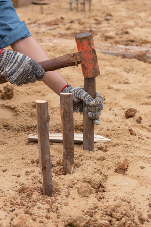 hammering: Worker hammering eucalyptus pointed at construction site
