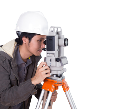 teodolito: ingeniero que trabaja con el equipo de encuesta teodolito en un trípode. Aislado en el fondo blanco