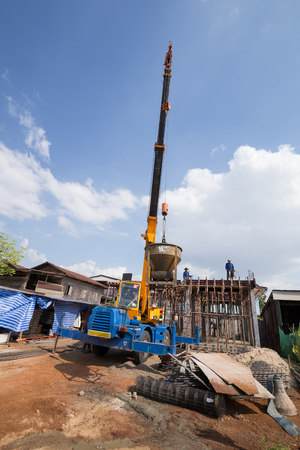 outside machines: NAKHON RATCHASIMA -DEC 24: worker casting concrete slab with mobile crane to build a house on December 24, 2015 in Nakhon Ratchasima, Thailand Editorial