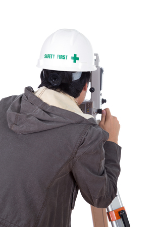 teodolito: ingeniero que trabaja con el equipo de encuesta teodolito en un tr�pode. Aislado en el fondo blanco