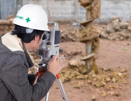teodolito: Los ingenieros utilizan taquímetro o teodolito con el fondo del emplazamiento de la obra Foto de archivo