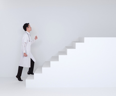 male doctor stepping up on white stairs