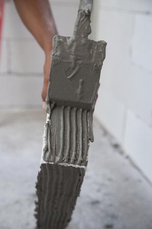 foamed: worker plastering lightweight Concrete block, Foamed concrete block, raw material for industrial wall or house wall