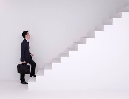 stepping on: Business man stepping up on stairs with wall background