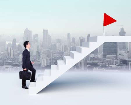 upstairs: Business man stepping up on stairs to red flag with city background (business success concept) Stock Photo