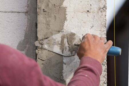 plasterer: plasterer concrete worker at wall of house construction at construction site Stock Photo