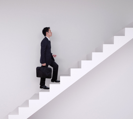 Business man stepping up on stairs with wall background