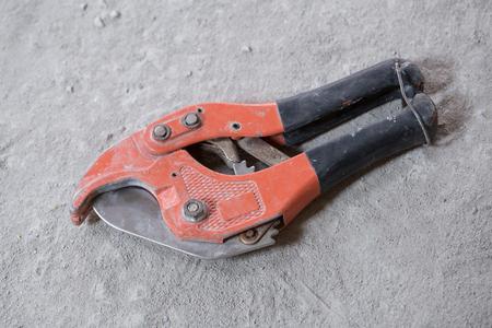 kunststoff rohr: rot Schere f�r Kunststoffrohr auf Betonboden Schneiden