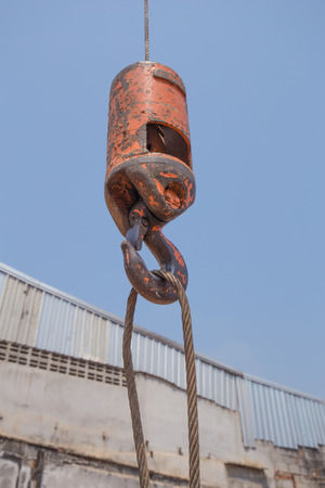 hoists: ranes hooks hanging on steel ropes with sky background