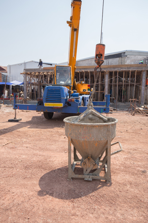construction material: Crane lifting concrete mixer container at construction site