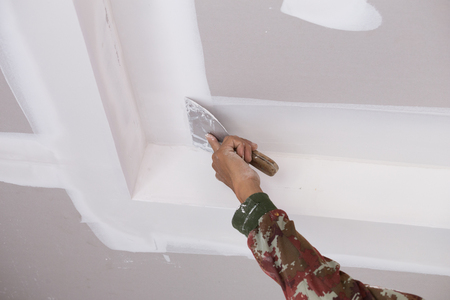 hand of worker using gypsum plaster ceiling joints at construction site Stockfoto