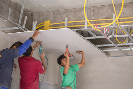 NAKHON RATCHASIMA -MAR 2: unidentified worker installing gypsum board ceiling of building house construction on March 2, 2016 in Nakhon Ratchasima, Thailand