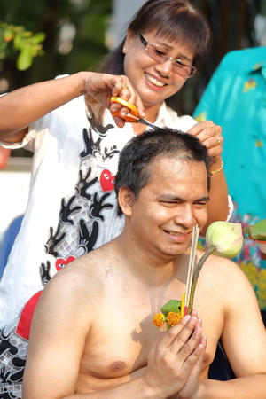 make belief: woman cut hair of man for be Ordained to new monk Stock Photo