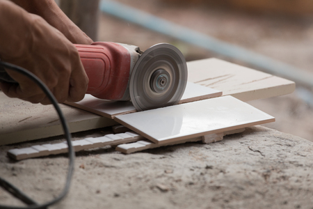 Worker Cutting A Tile Using An Angle Grinder At Construction Stock