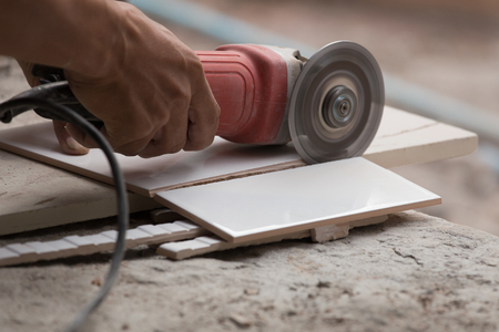 angle: worker cutting a tile using an angle grinder at construction site