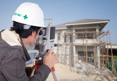 tacheometer: Engineers use tacheometer or theodolite with house construction site background