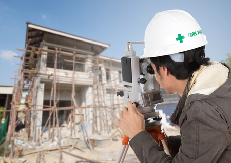 teodolito: Los ingenieros utilizan taqu�metro o teodolito con el fondo de la casa emplazamiento de la obra Foto de archivo