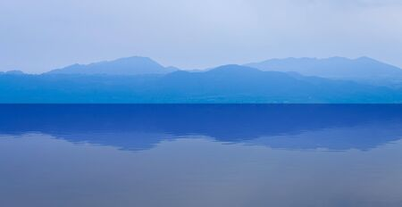 soft peak: group of blue mountain layers with water reflection in Thailand for background