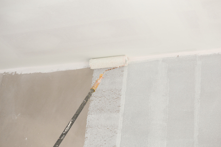 empty of people: painting a wall and ceiling with painting roller Stock Photo