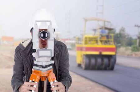 tacheometer: engineer working with survey equipment theodolite with road under construction background Stock Photo