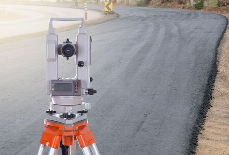 tacheometer: Survey equipment theodolite on a tripod.  with road under construction background