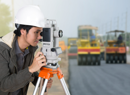 teodolito: engineer working with survey equipment theodolite with road under construction background Foto de archivo